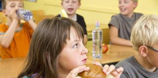Niños desayunando en el colegio con pan